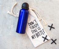 Бутылка девочка-подростка или мальчика установленная голубая сумки воды и ткани с литерностью Дон ` t касается этому моя бутылка  стоковое фото