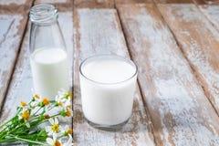 Бутылка и стекло молока на деревянном столе стоковые изображения