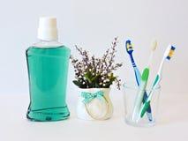 Бутылка и стекло mouthwash на полке ванны с зубной щеткой Зубоврачебная концепция гигиены полости рта Комплект устных продуктов з стоковое изображение
