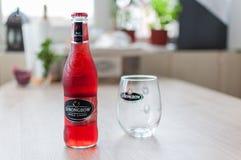 Бутылка и стекло Strongbow на деревянном столе стоковая фотография