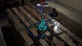Бутылка кальяна стеклянная для куря табака в кафах на столе с запачканной предпосылкой видеоматериал