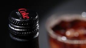 Бутылка кока-колы нул с падениями воды и стекла с кубами льда видеоматериал