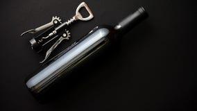 Бутылка красного вина и штопор на черной штейновой предпосылке стоковое изображение