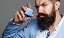 Бутылка кёльна моды Бородатый мужчина предпочитает дорогой запах благоуханием Духи человека, благоухание Мужское благоухание и стоковое изображение rf