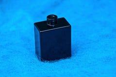 Бутылка малого черного стекла открытая стоит на голубых шерстях стоковые изображения rf