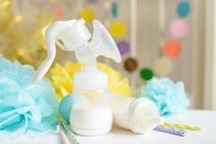 Бутылка младенца с грудным молоком, различным праздничным бумажным оформлением перед кроватью младенца Оно ` s концепция торжеств Стоковое Изображение