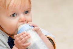 Бутылка молодого мальчика малыша выпивая стоковая фотография