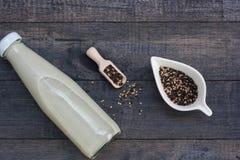 Бутылка молока сезама на черной деревянной предпосылке Стоковая Фотография