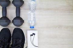 Бутылка питьевой воды, ботинки спорта, гантели, белое полотенце и наушники на деревянной предпосылке Стоковые Фото
