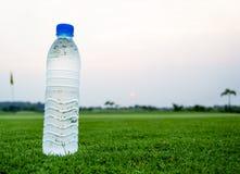 Бутылка питьевой воды на зеленом поле Стоковая Фотография RF