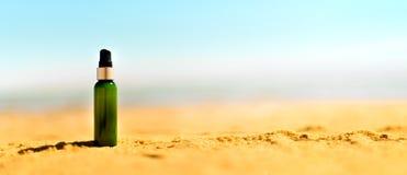 Бутылка солнцезащитного крема в песке против предпосылки моря с copyspace Обои каникул и перемещения Принципиальная схема внимате Стоковые Изображения RF