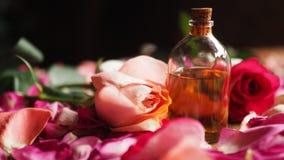 Бутылка стекла масла ароматности среди роз и лепестков на таблице, естественного сырья, выбранного фокуса стоковое изображение rf