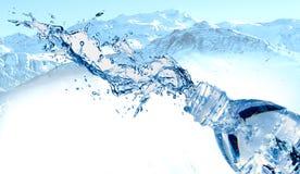 Бутылка с водой в выплеске воды, красивой снежной горе на задней земле стоковое фото