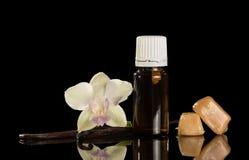 Бутылка с душистой жидкостью для курить, стручка и цветка ванили изолированных на черноте Стоковое Изображение RF