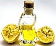 Бутылка с маслом лимона и 2 сжимали половины лимона против wh Стоковое фото RF