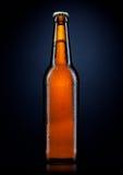 Бутылка холодного пива с падениями, на черноте Стоковые Фото