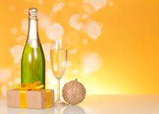 Бутылка шампанского, бокала вина, игрушек рождества и подарка, на желтой предпосылке Стоковое фото RF