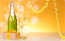 Бутылка шампанского, подарок ` s Нового Года на желтом цвете мерцающем Стоковые Фотографии RF
