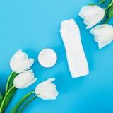 Бутылка шампуня, сливк и белые тюльпаны цветут на голубой предпосылке Блог красоты Плоское положение, взгляд сверху Стоковое Изображение RF