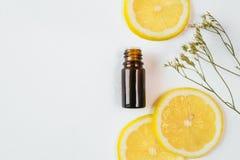 Бутылка 2 эфирного масла лимона на белой предпосылке стоковые фото