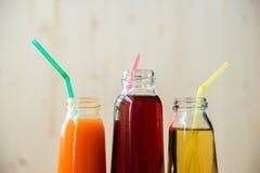 3 бутылки апельсинового сока и трубок на таблице на белой предпосылке, как много по мере того как 2 апельсина и один отрезок апел Стоковые Фотографии RF