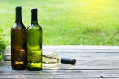 Бутылки белого вина на деревянном столе Стоковые Изображения RF