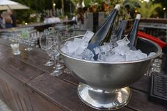 Бутылки белого вина на льде и близрасположенных пустых стеклах для вина Стоковое Изображение RF