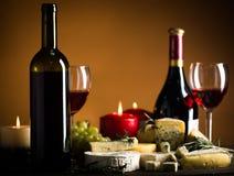 Бутылки вина, бокалы, свечи Lit, сыры Стоковое Изображение