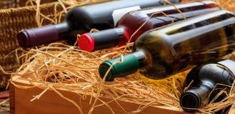Бутылки вина на предпосылке соломы Стоковые Изображения