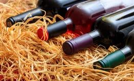Бутылки вина на предпосылке соломы Стоковая Фотография