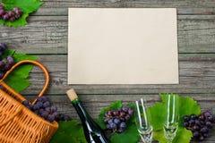 Бутылки вина с виноградинами, корзиной, 2 рюмками на деревянной предпосылке с старым бумажным шаблоном Стоковые Изображения RF