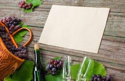 Бутылки вина с виноградинами, корзиной, 2 рюмками на деревянной предпосылке с старой бумагой Стоковое Изображение RF