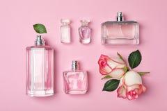Бутылки дух и роз на предпосылке цвета Стоковые Фото
