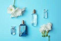 Бутылки дух и цветков на предпосылке цвета Стоковые Изображения