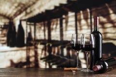 Бутылки и стекла вина в погребе Стоковое Изображение RF