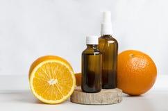 Бутылки косметик и свежие апельсины, деревянная доска против белой стены Концепция процедур спа стоковые фотографии rf
