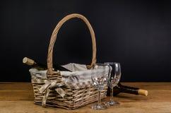 бутылки красного вина на плетеной корзине на деревянном столе Стоковое Изображение RF