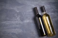 Бутылки красного и белого вина на темной предпосылке Стоковые Фотографии RF
