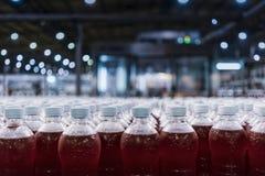 Бутылки красной соды в линии фабрики стоковое фото rf