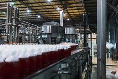 Бутылки красной соды в линии фабрики стоковые фото