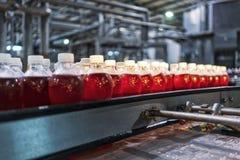 Бутылки красной соды в линии фабрики стоковое фото