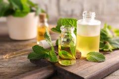 Бутылки листьев эфирного масла и мяты Стоковое Фото