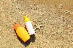 Бутылки лосьона с морскими звёздами на песке Стоковая Фотография RF