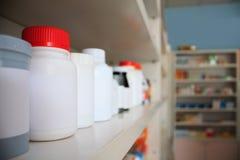 Бутылки медицины аранжированные на полке на аптеке Стоковая Фотография