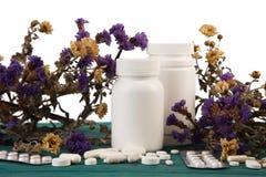 бутылки медицины на деревянном столе изолированном с цветком и pils Стоковое фото RF
