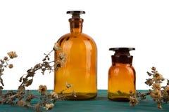 бутылки медицины на деревянном столе изолированном с цветком Стоковое фото RF