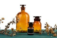 бутылки медицины на деревянном столе изолированном с цветком Стоковое Изображение RF