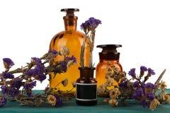 бутылки медицины на деревянном столе изолированном с цветком Стоковые Изображения RF