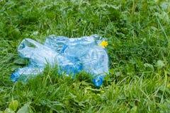Бутылки минеральной воды на траве в парке, засаривать окружающей среды Стоковая Фотография