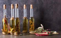 Бутылки оливкового масла с различными специями и травами Стоковое Фото